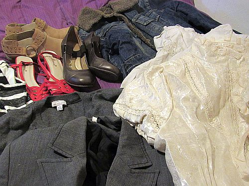 clothes & shoes lying on a bed
