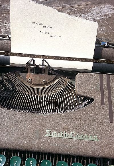 "A mid-20th century typewriter with a scrap of paper in it; the paper reads ""WisCon, WisCon, do you read?"""