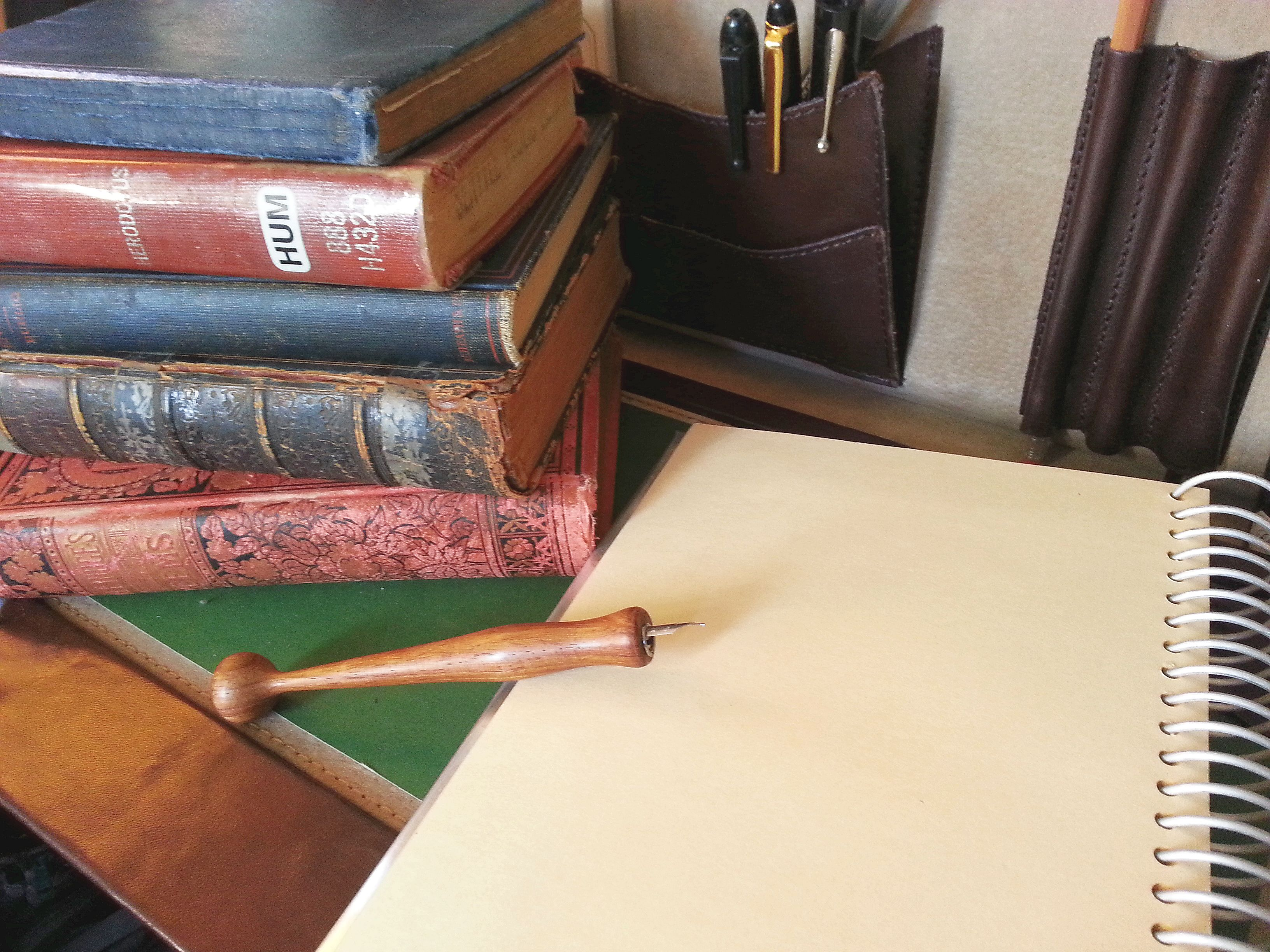 A pile of books stacked next to a notebook and a nib pen.