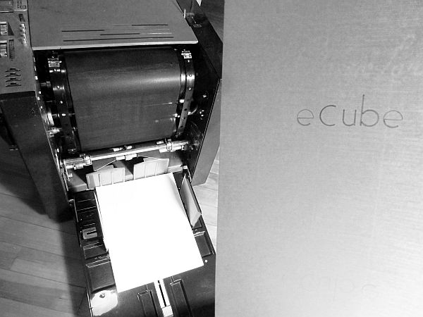 "An early 1990s mimeograph machine, and a sheet of white paper reading ""eCube""."