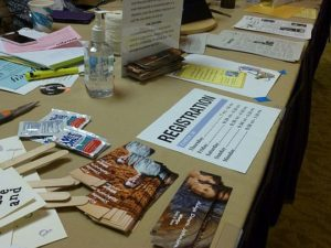 the Registration Desk -- gently cluttered with bookmarks, Registration info
