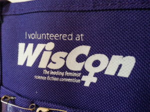 "A purple badge holder that declares ""I volunteered at WisCon"""
