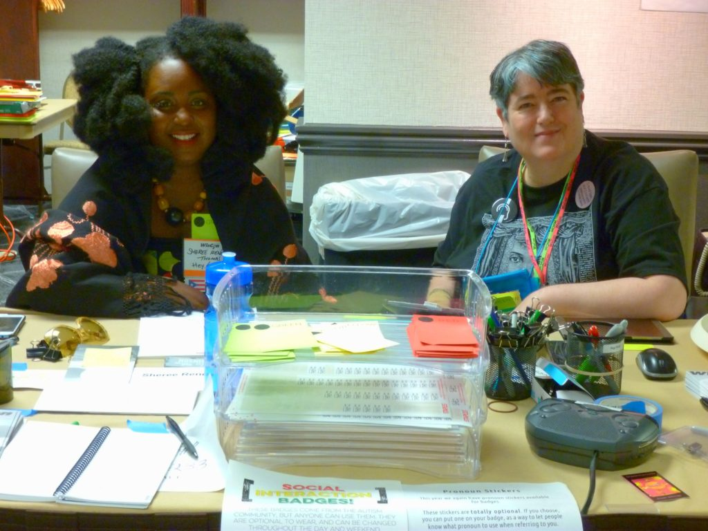 WisCon's registration desk, staffed by 2 volunteers